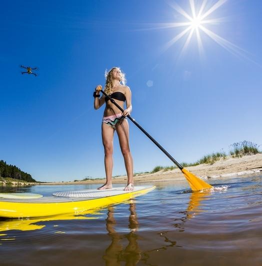 Drone AirDog mis en situation derrière une championne de paddle