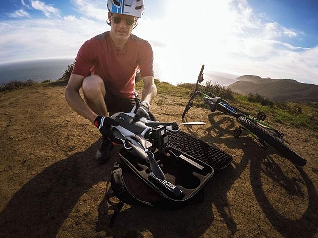 Cycliste en train de déployer le drone GoPro Karma