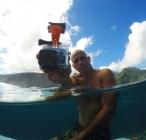 """Surfeur dans l\'eau, tenant sa fixation \""""Mouth Mount pour GoPro\"""" à la main"""
