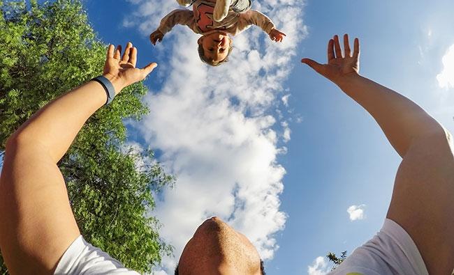 Vue d'un homme jetant son enfant et utilisant la télécommande vocale Remo pour Hero5 Black