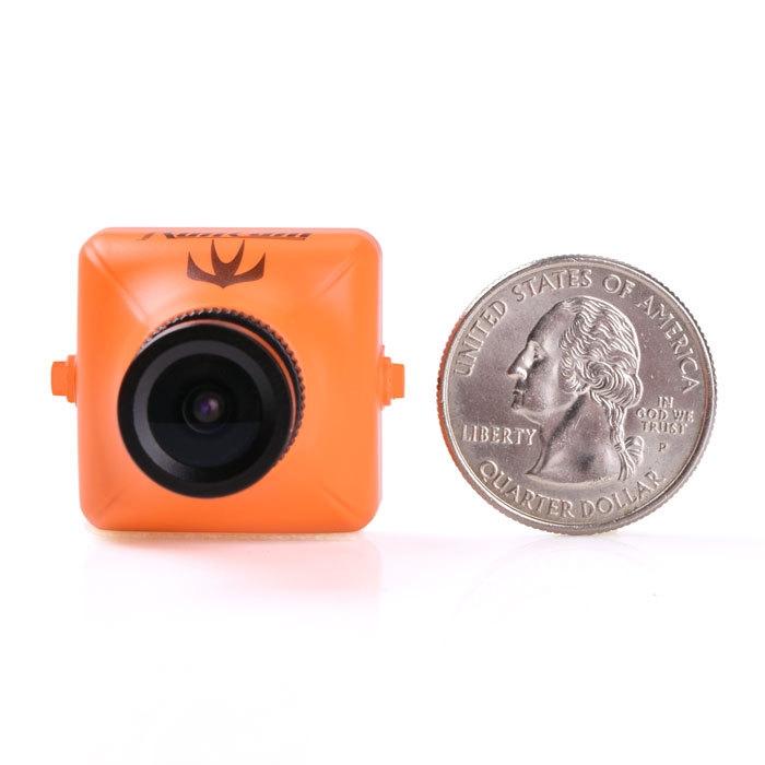 Caméra FPV RunCam Swift Orange comparée à une pièce de 25 cents.