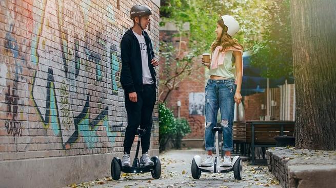Deux personnes dans la rue en train d'utiliser leur Gyropode Ninebot Mini - Xiaomi