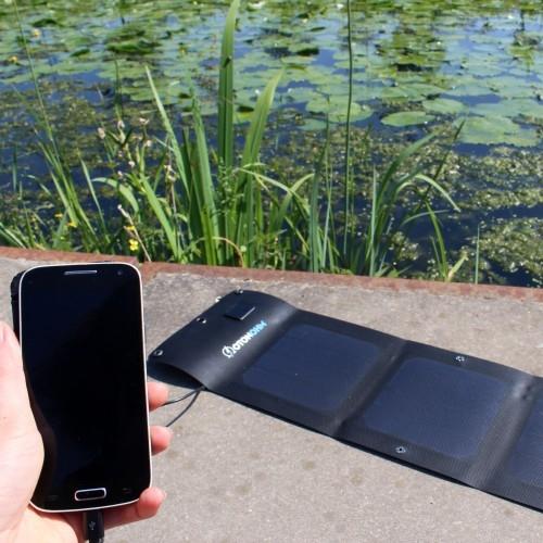 Panneau solaire Sun Charge branché à un smartphone en pleine nature