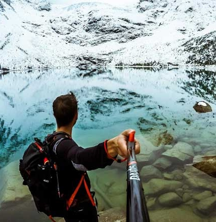 Perche à Selfie 180° Spivo tenue a la main face à un paysage de montagne